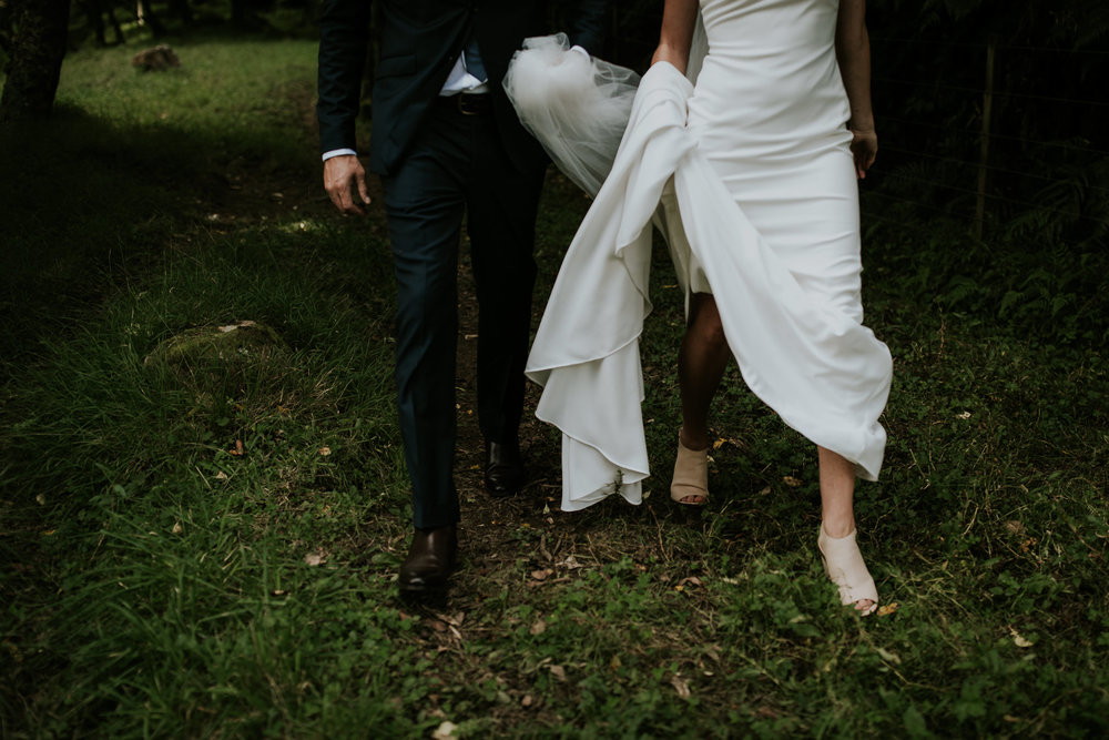 Shot of bride and groom walking through field holding dress after New Zealand first look