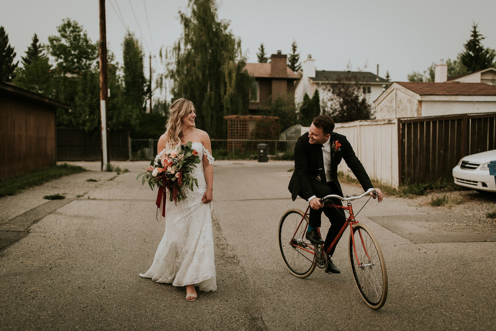 Romantic boho bride carrying beautiful bouquet while groom rides bike beside her down Calgary alley