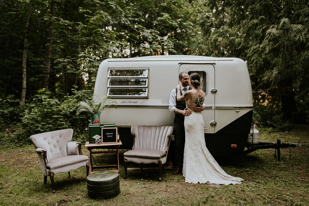 Edgy, tattooed bride and groom in front of vintage trailer on beautiful styled property on Vancouer Island