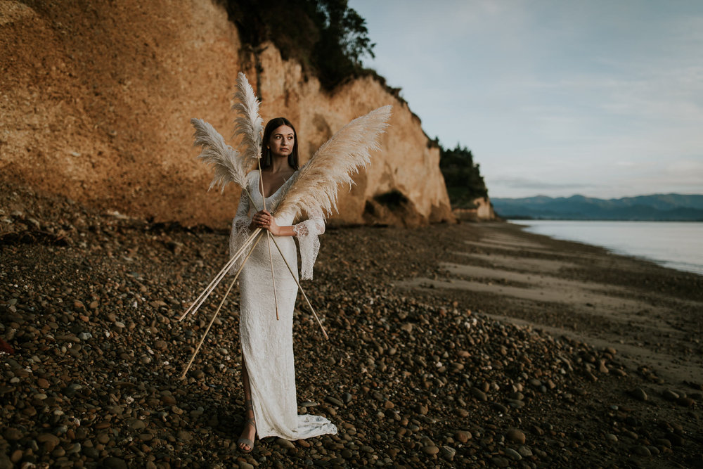 Bride wearing stunning Grace Loves Lace gown and holding Toi Toi on New Zealand beach elopement