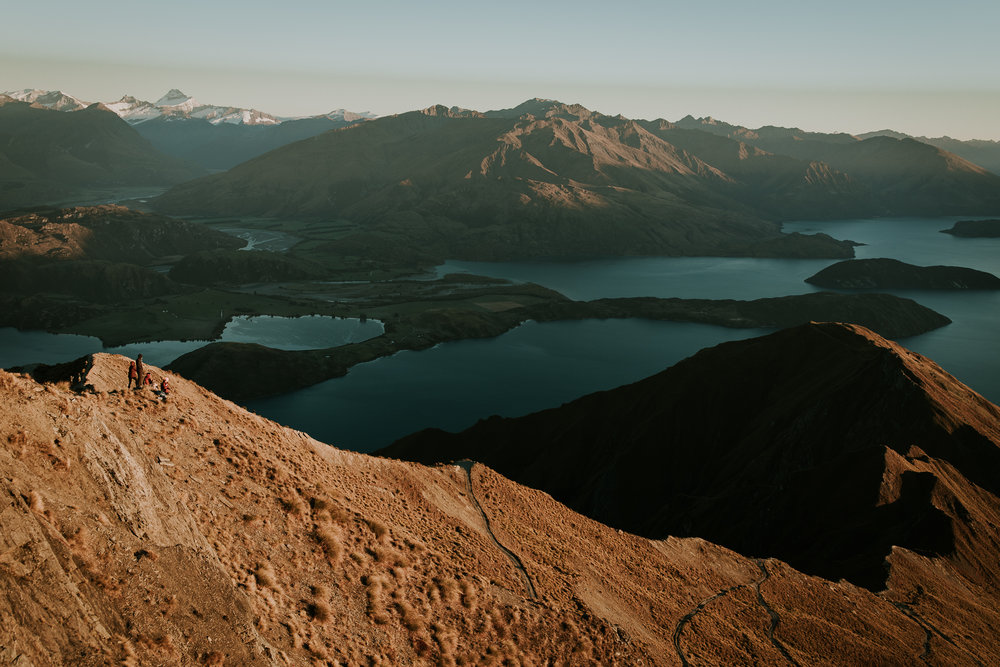 Tiny people hiking the challenging trail to Roys Peak at sunrise near Wanaka, New Zealand