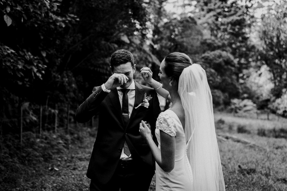 Bride wiping away grooms tears during emotional first look before Katikati destination wedding NEw Zealand