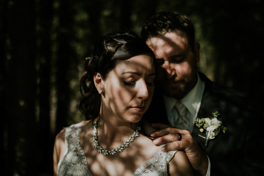 Bride and groom standing in the shadows of some trees with interesting shadows falling on face after Kananaskis wedding