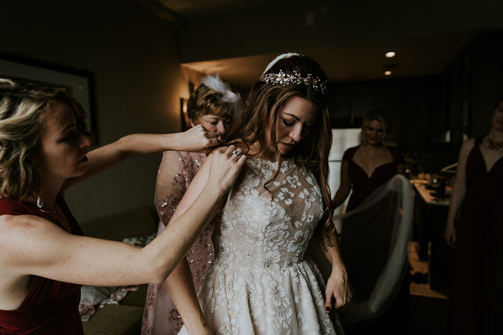 Bride getting help putting on her wedding dress from mother and bridesmaids before wedding at the commons calgary