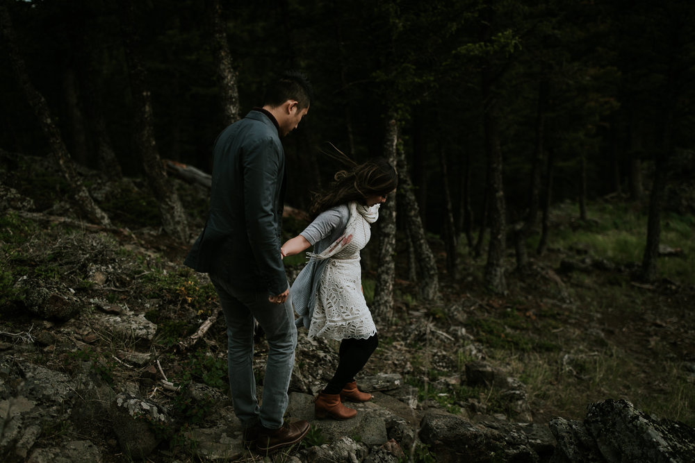Newly engaged couple holding hands and walking down cliffside, hair blowing in the wind near Fernie BC