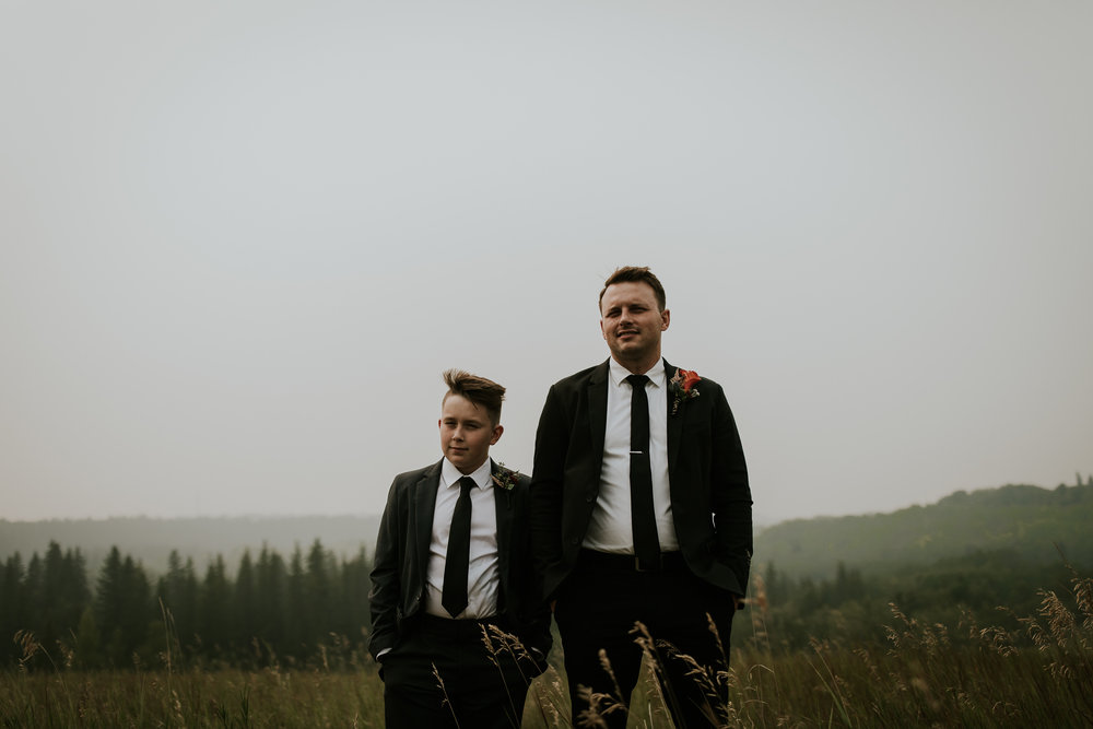 Groom and his son wearing suits and standing in long grass field on Calgary wedding day