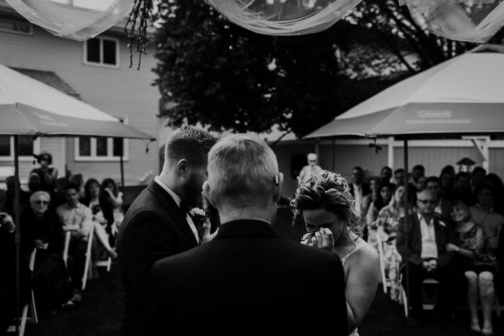 Photo of bride crying, and groom, taken from behind the officiant during intimate backyard wedding ceremony in Calgary