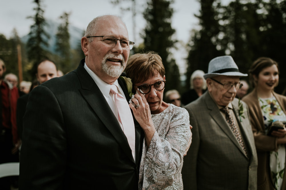 Mother and father of the bride wiping away tears during emotional wedding ceremony at Silvertip Resort Canmore Alberta