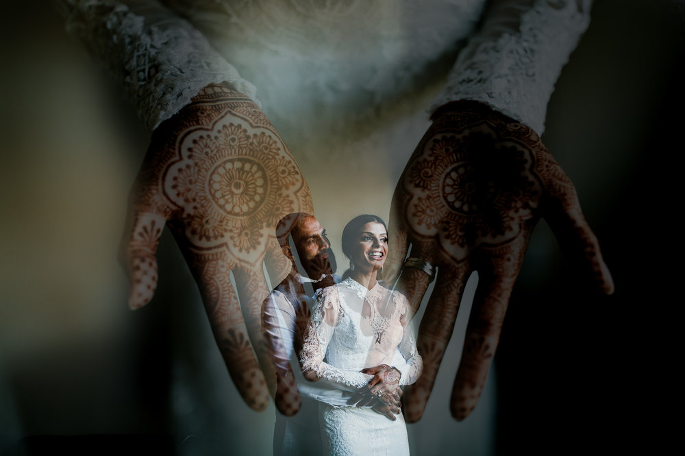 Double exposure of East Indian bride and groom embracing before their wedding ceremony with henna tattoos on hands before Whistler wedding