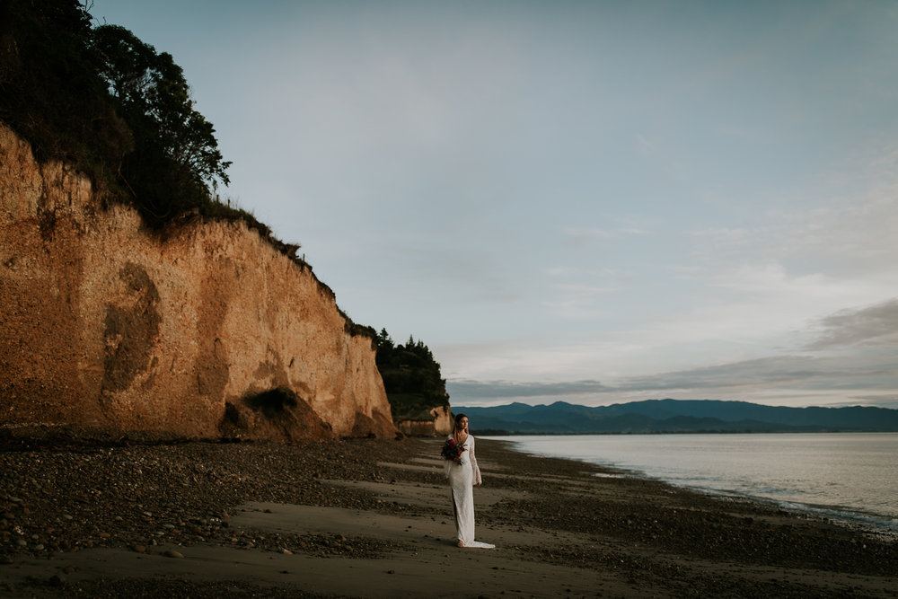 Solo bridal portrait of bride wearing Grace Loves Lace and holding wild bouquet after destination wedding on South Island New Zealand
