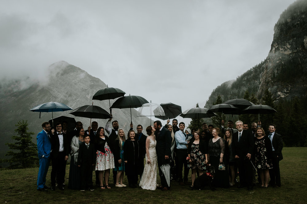 Family photo during rainy wedding day in Tofino BC with whole family holding umbrellas while bride and groom kiss in the middle