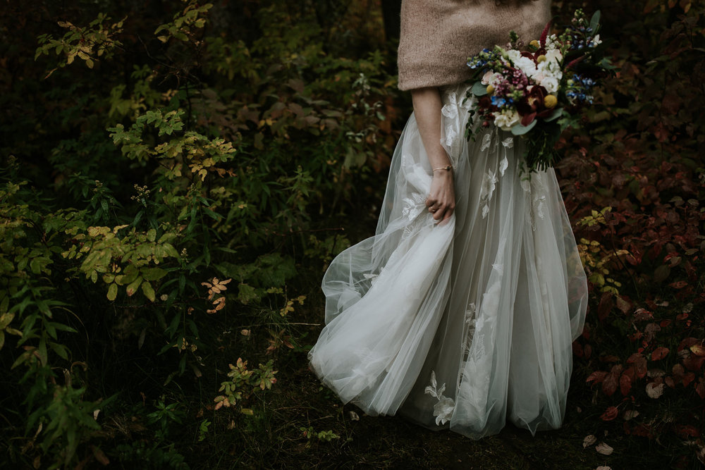 Fairytale bride holding dress and bouquet and walking through long grass during fall wedding in Kananaskis