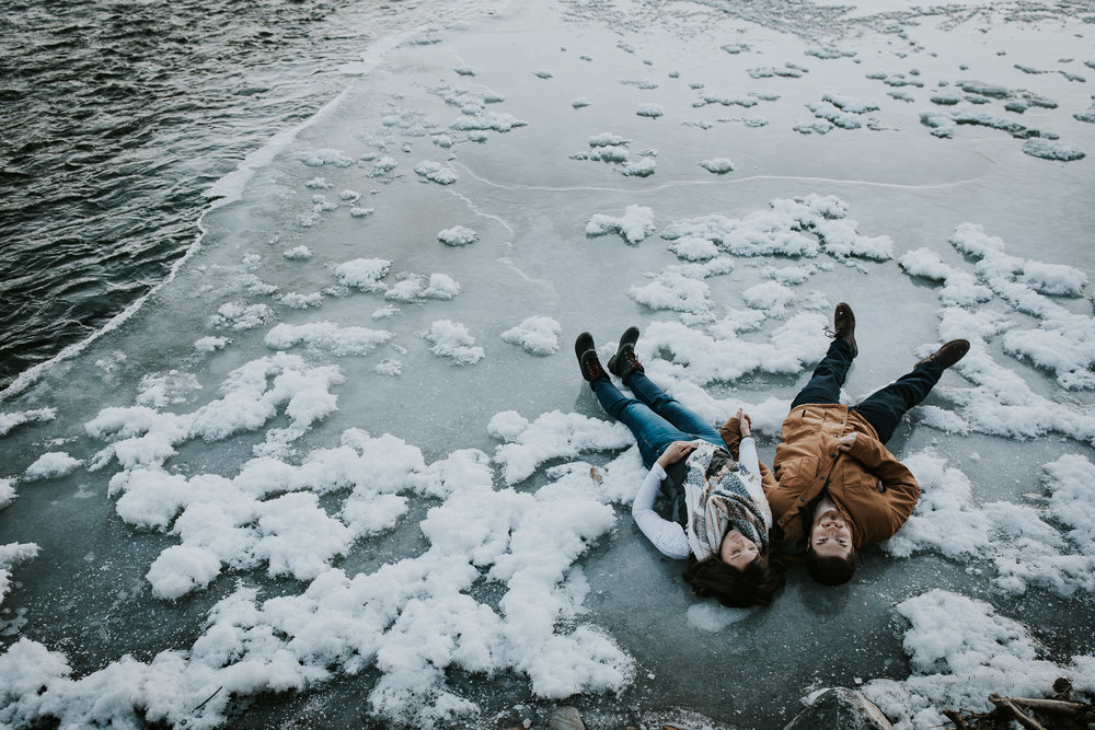 Calgary engaged couple holding hands and laying on patch of ice near Elbow River during winter engagement session