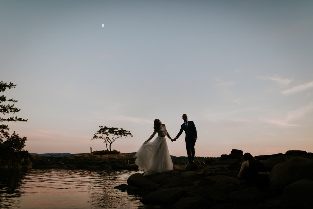 Bride and groom holding hands at sunset as moon rises over Gabriola island after destination wedding at Bodega Ridge, Canada