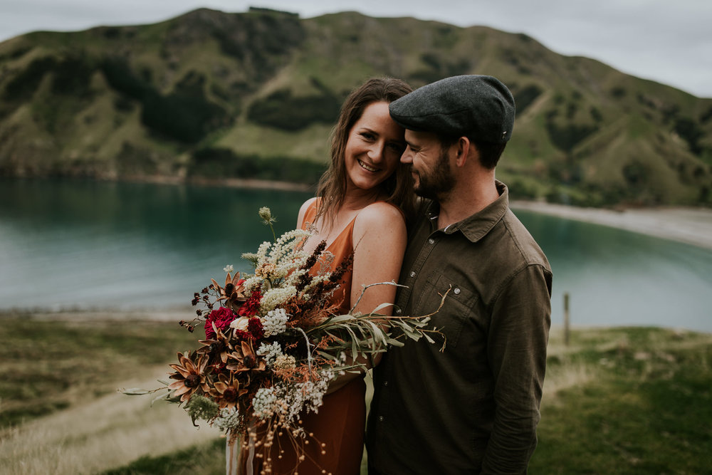New Zealand destination wedding photographer being photographed during engagement shoot along cliffs of South Island New Zealand