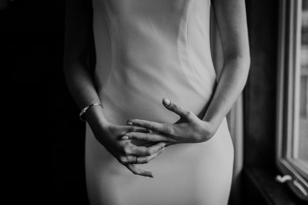 Black and white portrait of bride nervously playing with hands before intimate wedding ceremony in Canmore Alberta