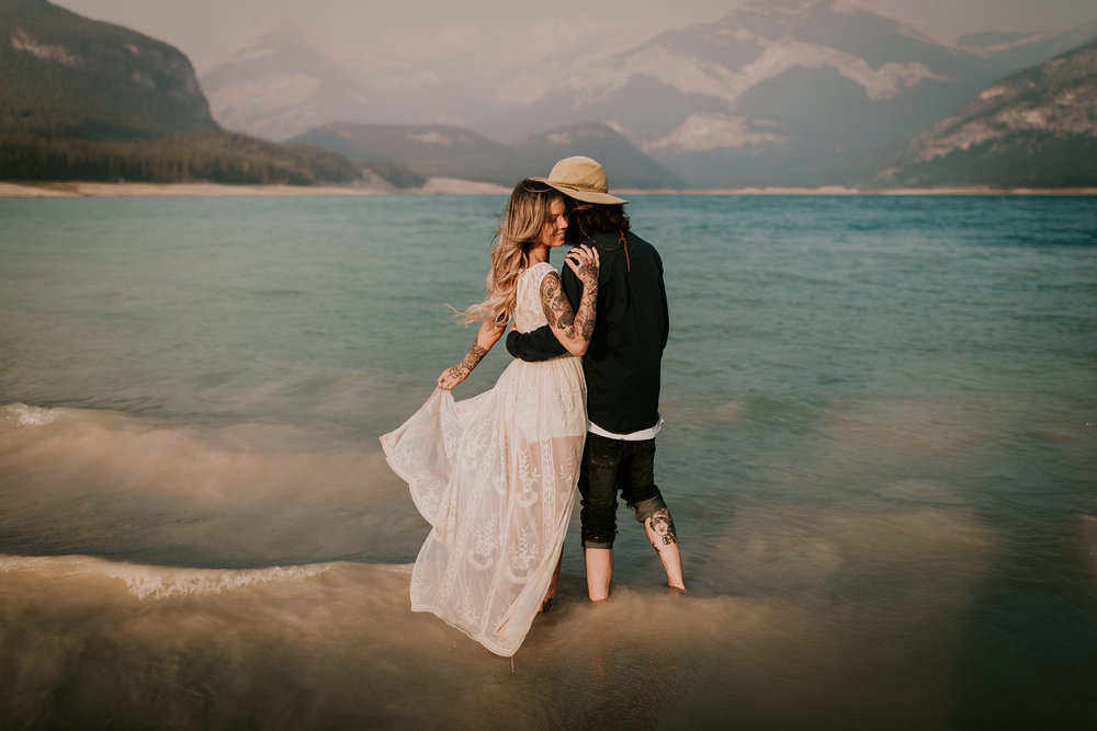 Magical sunrise engagement session in Kananaskis with tattooed couple standing in the water as sky turns pink