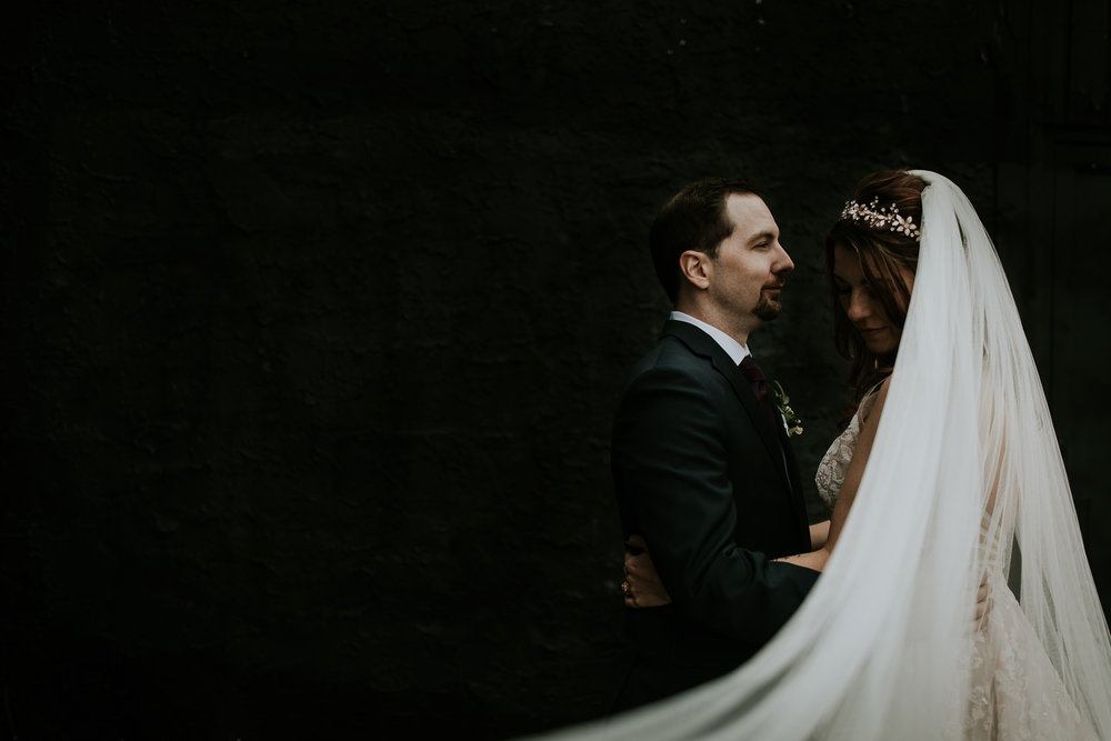 Fine art, moody portrait of bride and groom with veil creating artistic quality after Commons wedding Calgary