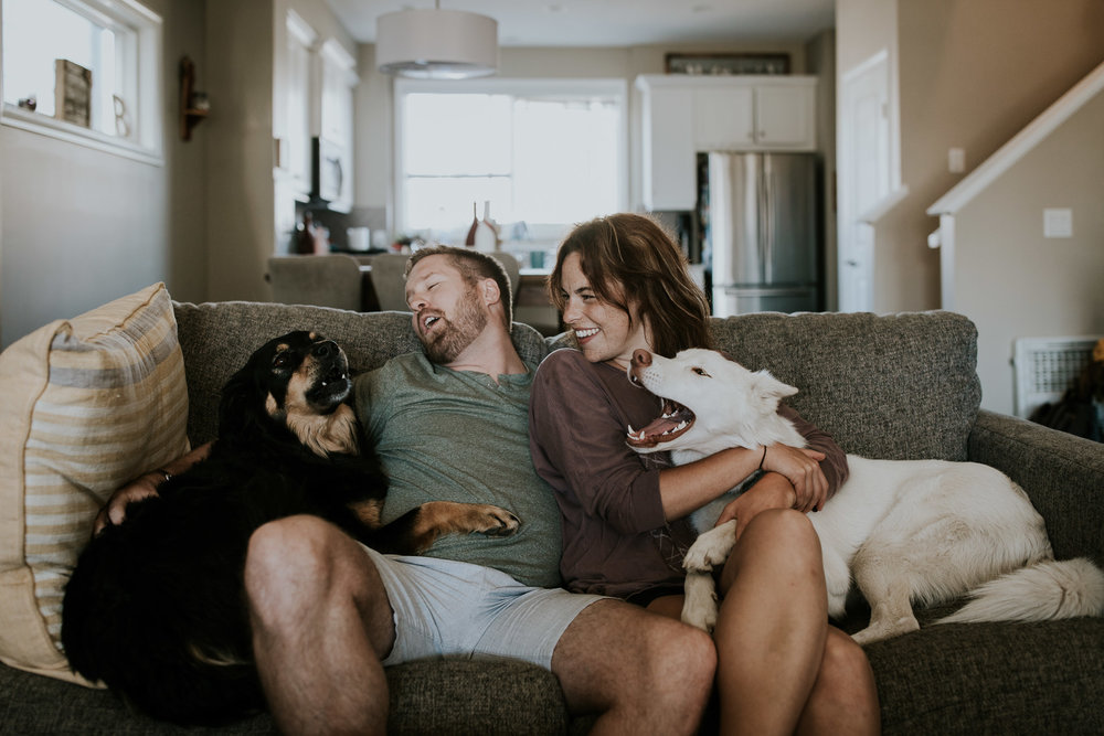 Newly engaged couple howling with their dogs on their couch during intimate at home engagement shoot in Calgary AB
