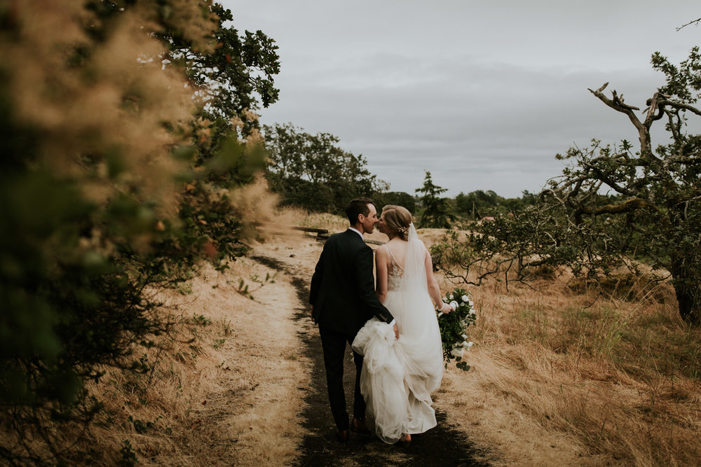 Newlywed couple walking down path in Victoria BC after intimate wedding ceremony on Vancouver Island