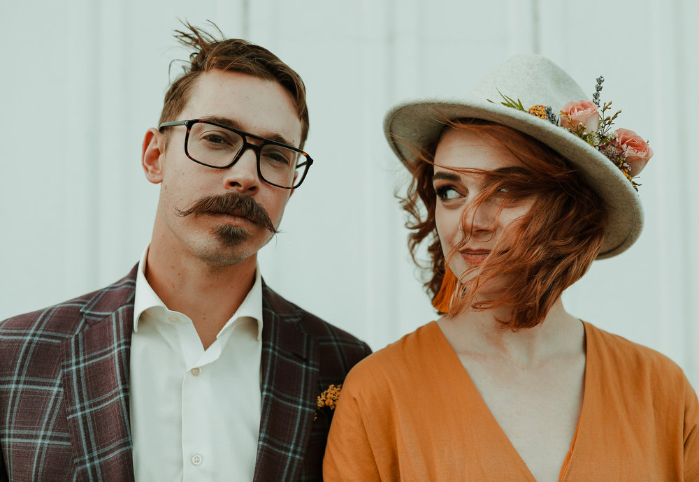 Quirky and alternative couple wearing glasses and a hat looking at the camera as hair blows in girls face