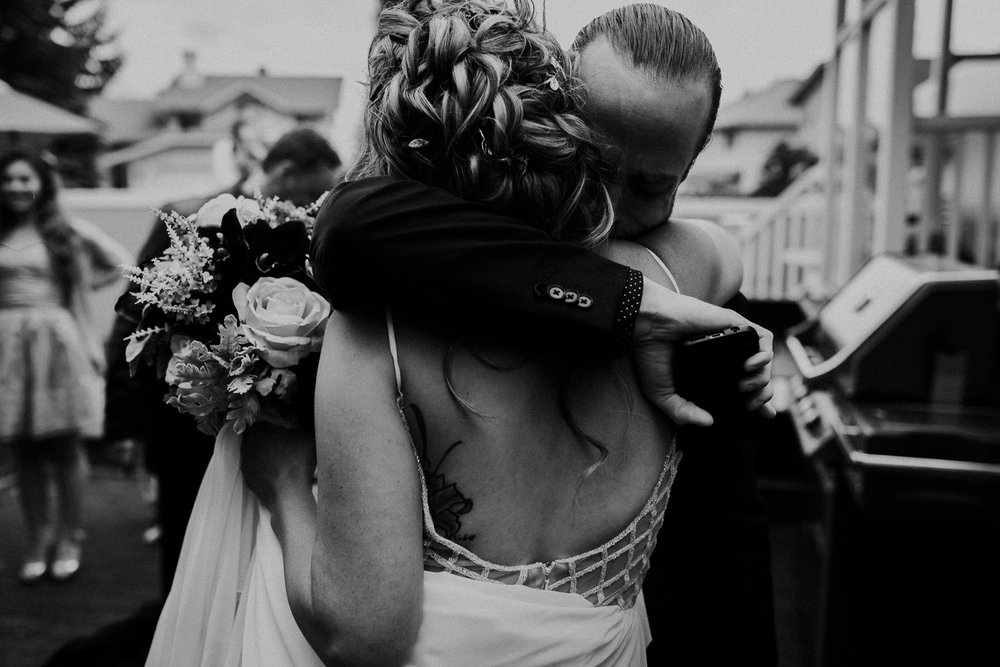 Black and white portrait of brides brother giving her an emotional hug after intimate backyard wedding ceremony in Calgary AB