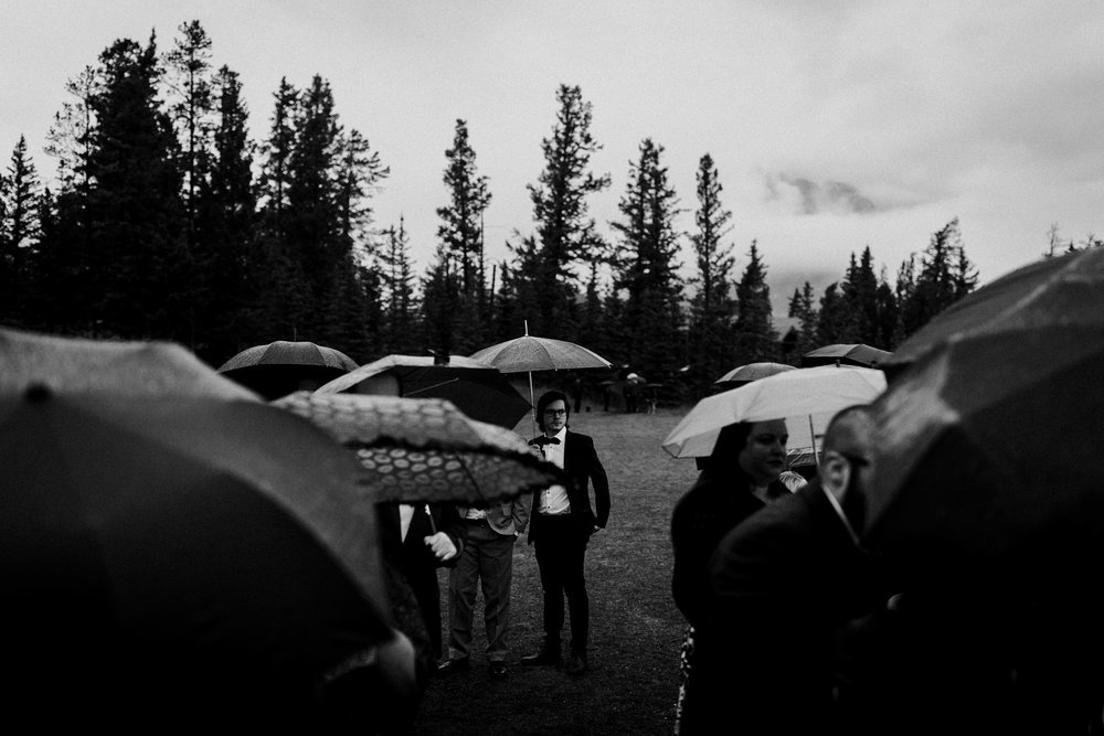 Moody black and white portrait of wedding guests all holding umbrellas with one guest being seen in the distance looking at the camera