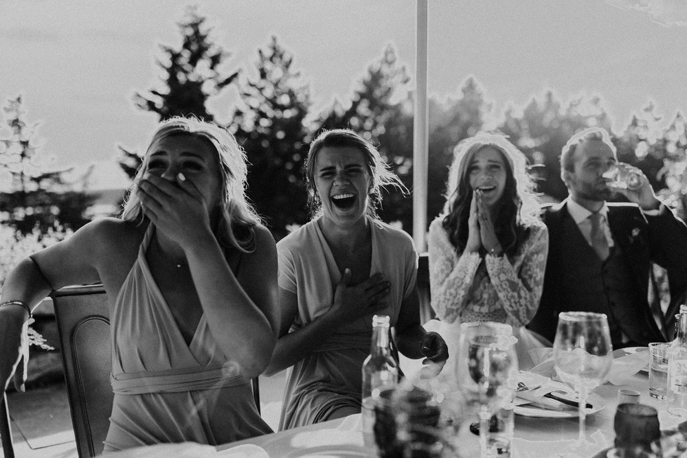Black and white portrait of head table including bride and groom laughing hysterically during speeches at Bodega Ridge destination wedding on Galiano Island, BC