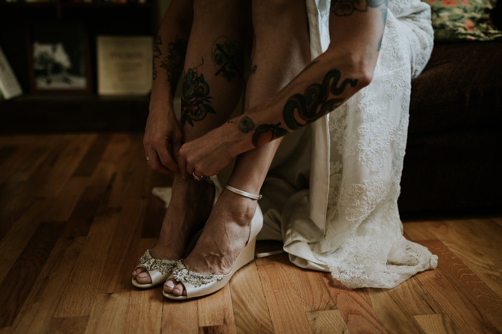 Close up of tattooed bride doing up her beautiful shoes before styled vintage wedding on Vancouver Island