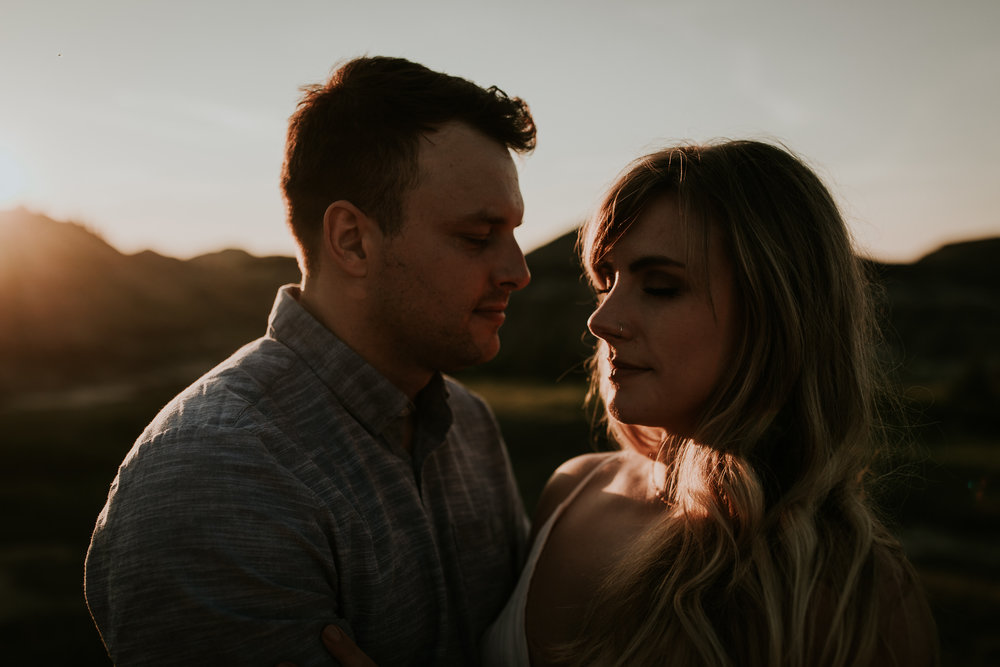 Moody, creative fine art portrait of newly engaged Calgary couple taken at sunset at Drumheller Alberta