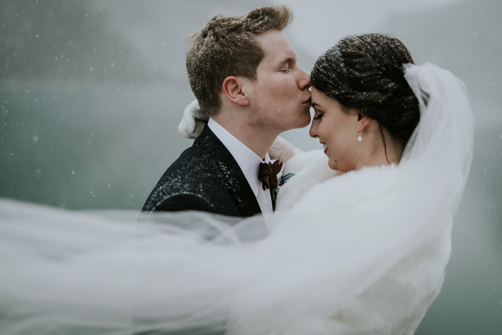 Beautiful couple embraces during snow storm at White Mans Pond in Canmore AB during elegant winter wedding