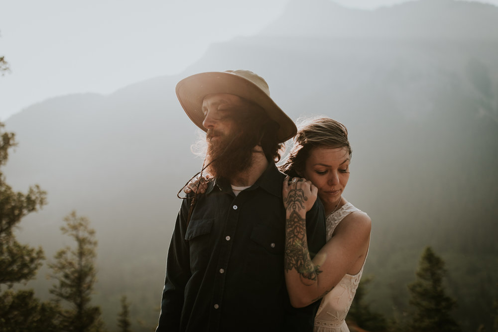 Beautiful tattooed couple embraces on top of cliff in Ireland as golden hour sunlight rises above the mountains