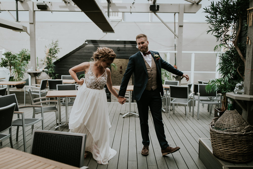 Bride and groom holding hands and showing off silly dance moves during intimate backyard wedding Calgary Canada