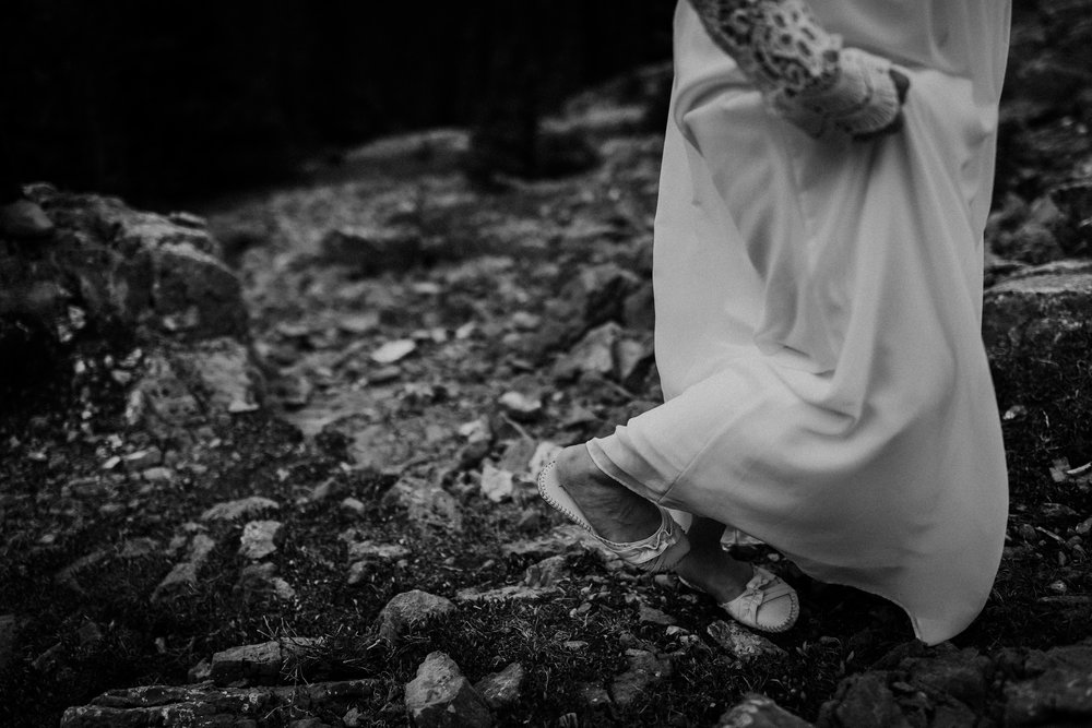 Black and white photo of bride holding dress and walking across rocks during mountain top elopement ceremony in Banff National Park Canada
