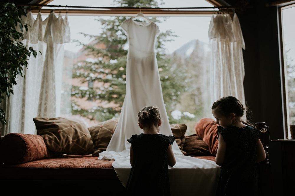 Young flower girls admire elegant bridal gown hanging in window of Fernie Ski Resort home before Fernie winter wedding