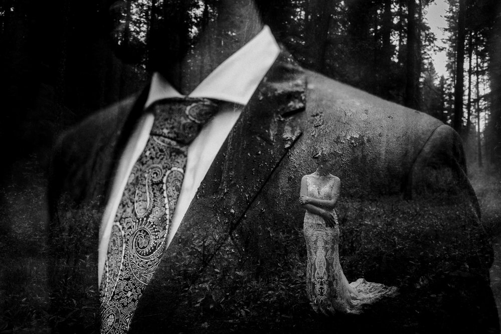 Double exposure black and white portrait of bride holding herself and soaking wet grooms suit after rainy June wedding Canmore AB