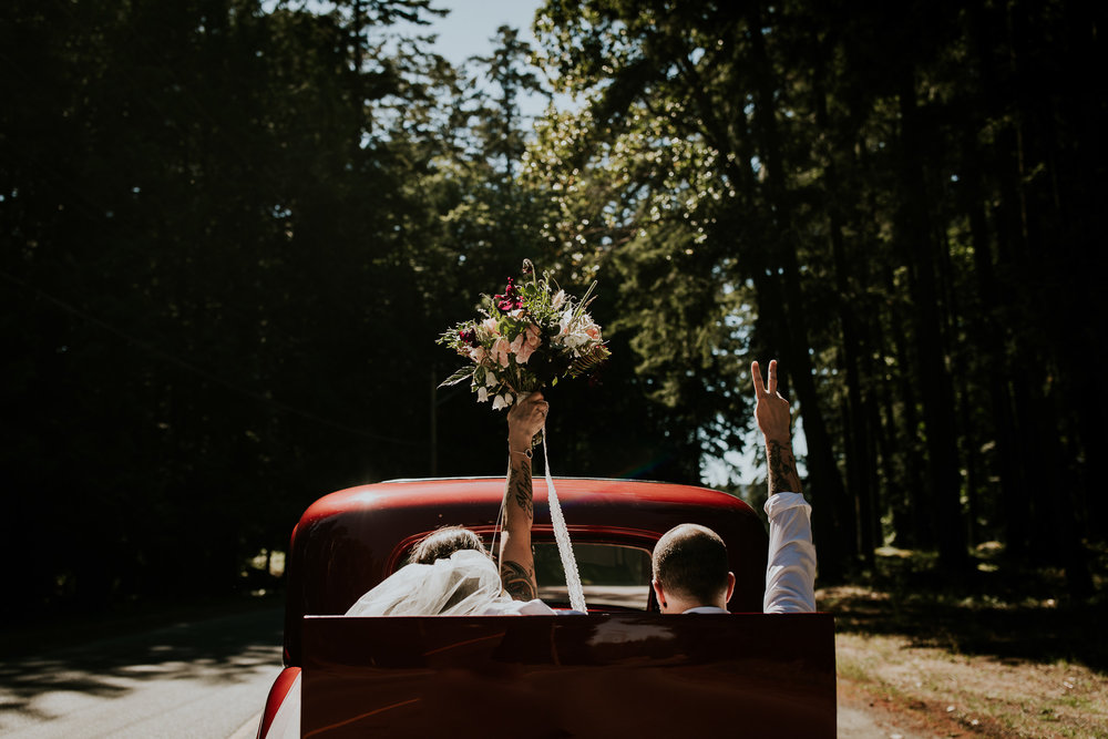 Edgy, tattooed bride and groom driving away in red classic car throwing bouquet and peace sign in the air after Tofino destination wedding