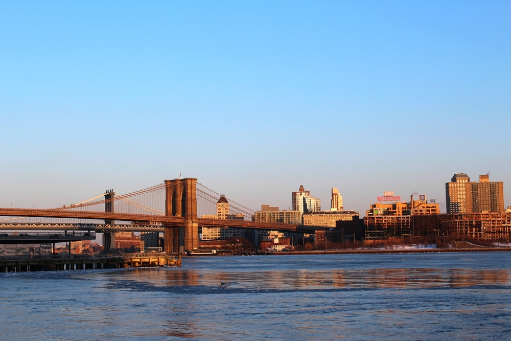 Het uitzicht van Lower East Manhattan over the Brooklyn Bridge en Brooklyn bij zonsondergang.