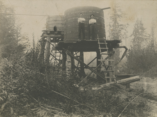 E. A. Persson and a work partner standing on newly finished gravity fed water tanks. (1910-12)