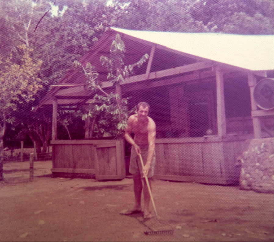 Ralph raking the leaves in front of our jungle home.