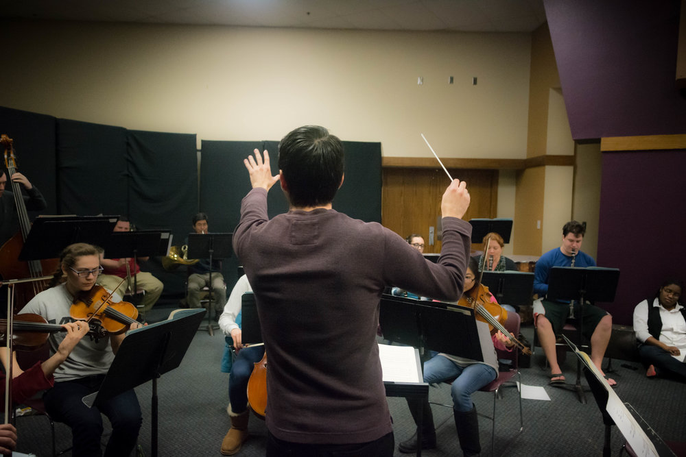 Alumnus '16 Enrique Quezada directs the orchestra for this live-music operatic comedy. | PC: Zach Morrison