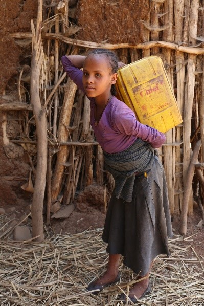 Nitsuh Amsalu, 13, carries water back home after collecting it from a hand dug well.