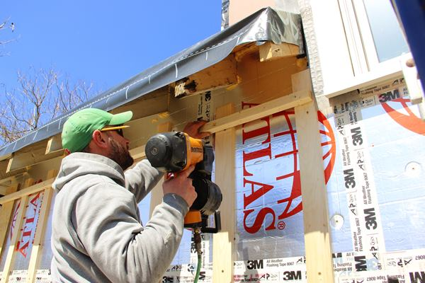 Carpenter Shane Fenton applies a a soffit nailer over the rain screen wall strapping.