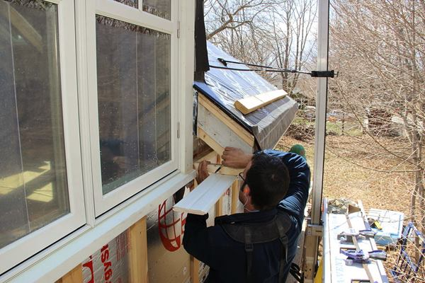 Pollard scribes a cut line onto the soffit board as Fenton holds the other end of the board in place.