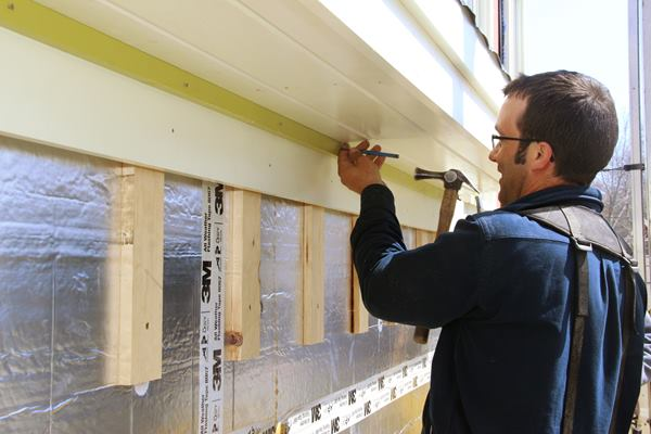 As a final touch, Pollards fastens pre-painted bed molding is over the frieze, setting the nails flush to the surface of the trim. The whole trim package will get a final coat of paint once the siding is complete.