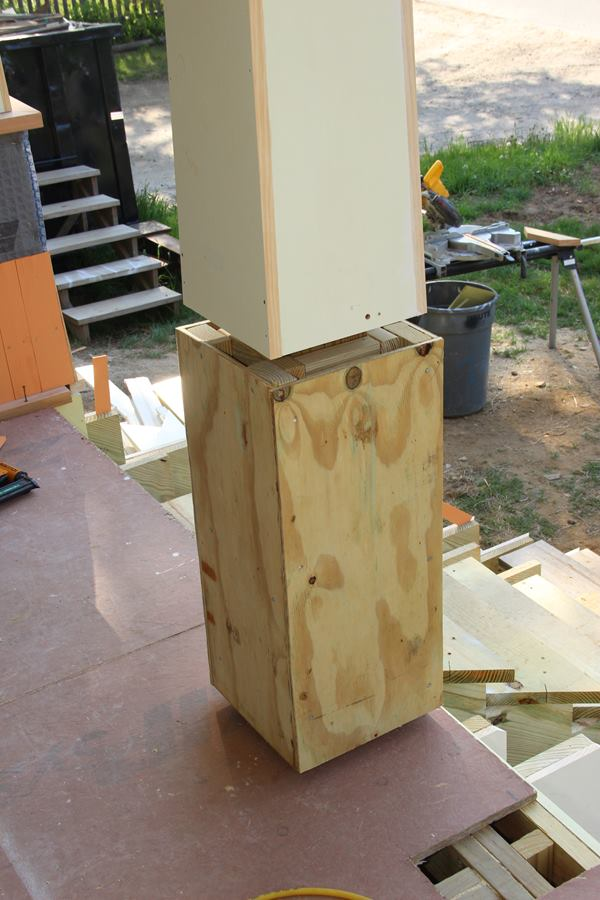 The base of the porch columns are boxed out with treated 2x4 blocking and treated plywood.