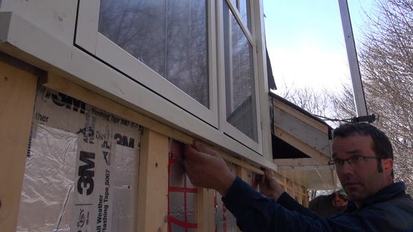 Pollard places a thin spacer under the soffit and window trim, padding out the wall to allow an exhaust point for air movement in the cavity behind the siding and trim in the rain screen assembly.