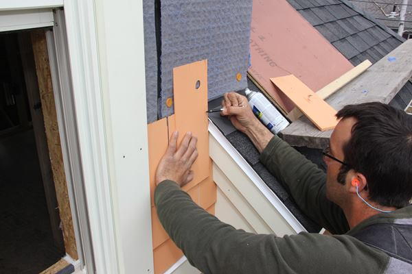 Pollard holds a shingle in place and freehand-scribes the profile of the adjacent roof edge onto the shingle.