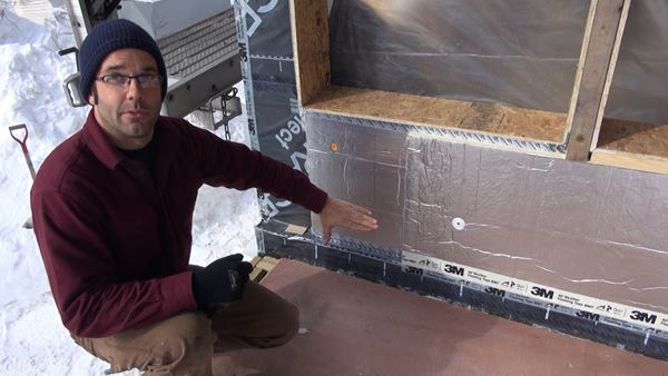 "Pollard explains the exterior air barrier and insulation assembly on a freezing cold day in February after a succession of blizzard snowstorms. Visible here are OSB bucks used to extend the window openings; Grace polyethylene and bitumen membrane applied as an air and vapor barrier to the existing board wall sheathing, and integrated into the Grace membrane inserted earlier as a capillary break at the joint between the foundation and the floor frame; a 1.5-inch layer of foil-faced polyiso insulation appied over the air barrier membrane, attached with cap nails (joints sealed with Dow Weathermate tape); and a top layer of 1.5-inch foil-faced polyiso attached with four-inch screws and washers (joints sealed with 3M 8067 flashing tape). Not yet installed here are beveled clapboards in the window sill openings to create sloped drainage, which will be topped with more membrane integrated into the drainage plane formed by the foil-faced foam. ""We're not doing that yet because we don't want it to get beat up before we put the windows in,"" said Pollard."