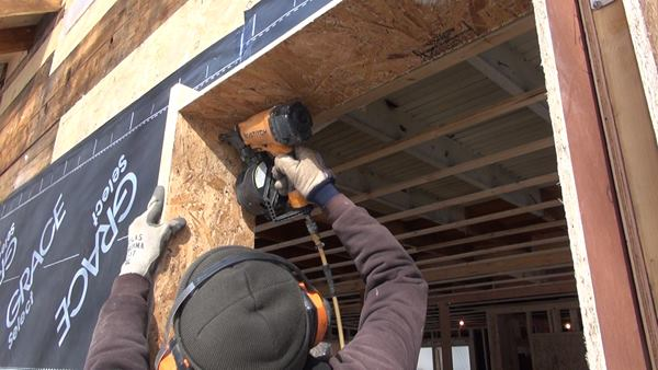 Using a 3-inch rip of 2x4 as a depth gauge, carpenter Ed Muennich nails an OSB extension window buck into the existing wall framing.